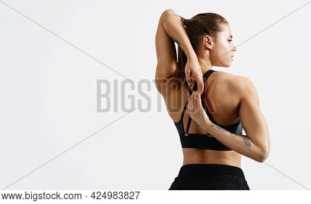 Rear View Of Fit And Sporty Fitness Woman Stretching Arms And Back Before Workout Exercises. Woman B
