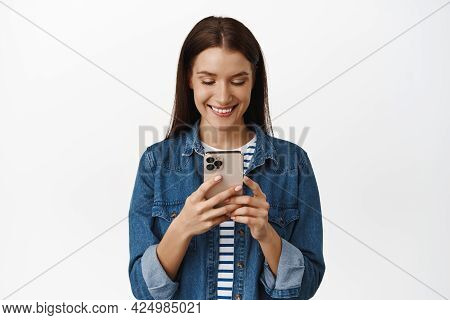 Young Happy Woman Holding Mobile Phone, Smiling While Texting, Using Smartphone App Or Watching Vide