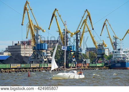Vyborg, Russia - August 08, 2016:  Small Sailing Yacht Sails Past A Cargo Port