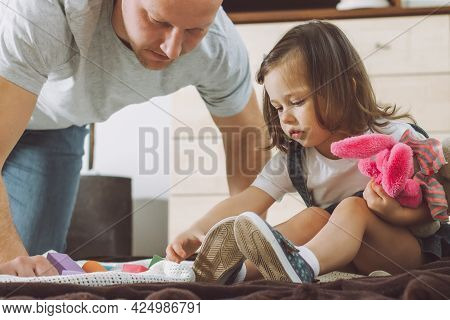Dad And Little Girl 2-4 Play With Constructor And Soft Toys Sitting On Floor At Home
