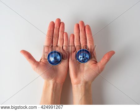 In The Men's Hands Are Two Blue Aluminum Coffee Capsules. One Of The Capsules Is Used. White Backgro