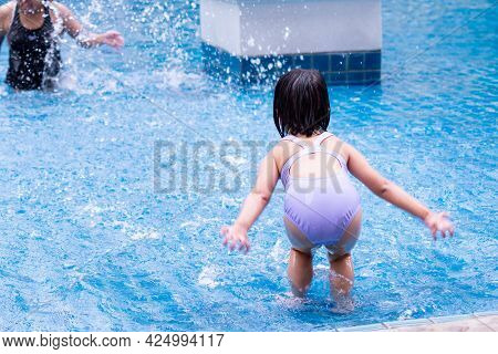 Rear View Of Asian Cute Baby Girl Is Splashing Water From A Pool On Her Mother. Children Play In The