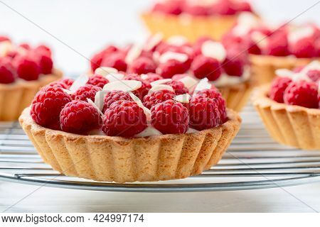 Delicious Raspberry Mini Tarts (tartlets) With Vanilla Custard Cream Sprinkled With Almond Flakes. C