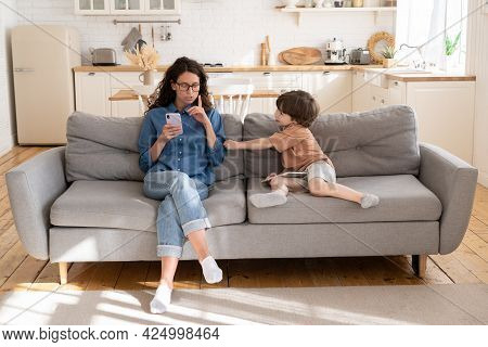 Young Mom Or Babysitter Use Smartphone Ask Little Kid To Be Quit And Calm. Bored Child Disturb Mothe
