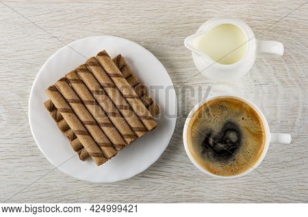 Brown Striped Wafer Rolls With Chocolate Filling In White Plate, Pitcher With Milk, Black Coffee In