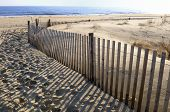 Beach fence and sand dune brightly lit by early morning sun. poster
