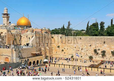 JERUSALEM - AUGUST 21: People at Western Wall as Dome of the Rock mosque on background. Both religious sites are sacred and most important for jews and muslims in Jerusalem, Israel on August 21, 2013.