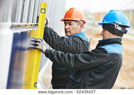 Plasterer builder worker with level examining granite stone marble facade works