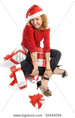 Pretty girl in red dress is holding presents. Isolated on white.