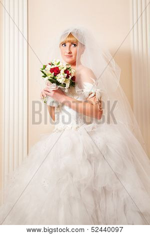 Beautiful blond woman in a magnificent wedding dress. Vertically framed photo.