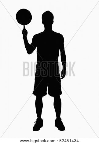 Silhouette of basketball player spinning basketball on finger.