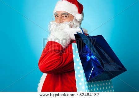 Lets go shopping with Santa this Christmas. Kris Kringle carrying shopping bags. poster