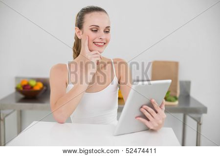 Thinking happy young woman using her tablet at table in the kitchen at home