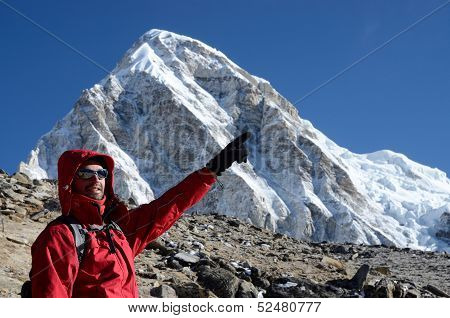 Young climber standing near Kala Patthar mountain and showing to Everest summit