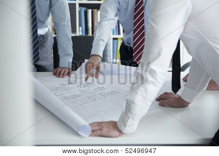 Two architects discussing over a blueprint in the office