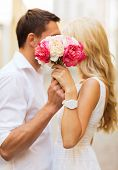 summer holidays, love, relationship and dating concept - couple with bouquet of flowers in the city poster