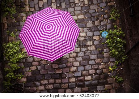Unrecognizable female under umbrella walking on paved street