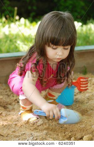 The Girl Playing To A Sandbox