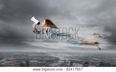 Young businesswoman with megaphone flying high in sky