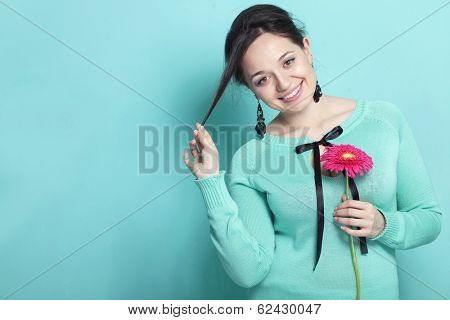 Portrait of woman holding pink herbera