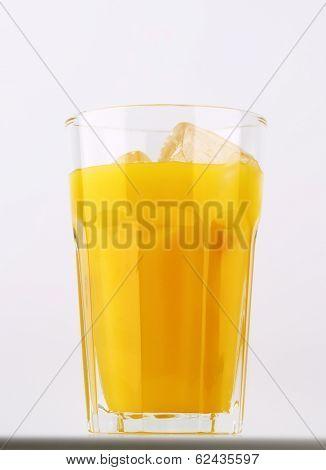 glass of fresh orange juice with ice cubes