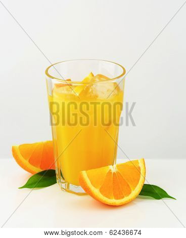 glass of orange juice with fresh orange and leaves