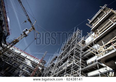 building and construction site, deep blue sky, scaffolding and cranes