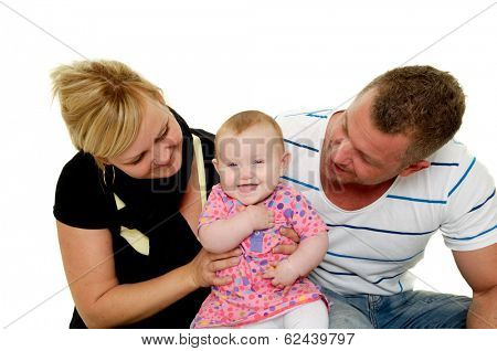 Happy smiling and laughing family. Mother and father are looking at their sweet smiling 4 month old baby.