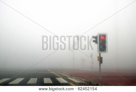 Fog in Dubai road. Red signal is on.