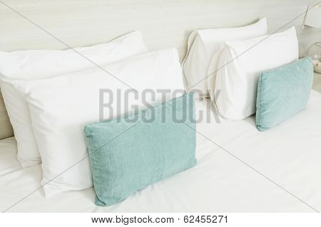 White And Green Pillows On Bed