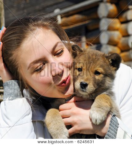 Young Beautiful Girl Kisses A Puppy