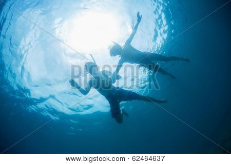 Couple snorkeling in a blue tropical sea