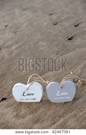 Couple Of Inscribed Wooden Love Hearts In The Quick Sand