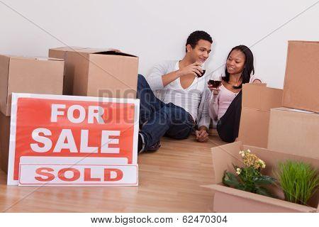Couple Sitting Among Boxes Making Celebration
