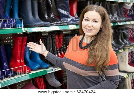 Woman Salesman Standing Near Store Shelves And Showing Waterboots