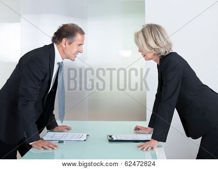 Mature Businessman And Businesswoman Looking At Each Other With Angry poster