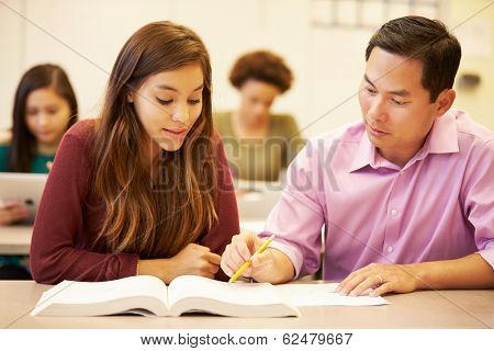Female High School Student With Teacher Studying At Desk