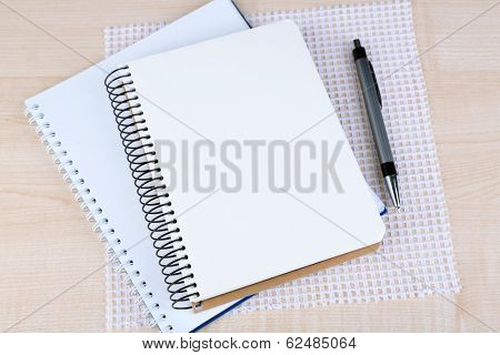 Notebooks with pen on color wooden background