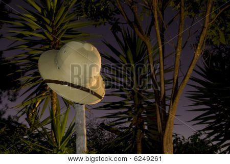 Pith helmet on stick at night