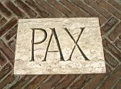 huge inscription PAX as a symbol of peace on a plaque in the midst of bricks poster