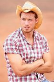 Cowboy man handsome and good looking with hat in rural USA countryside. Male model in american western prairie landscape nature on ranch or farm in USA. poster