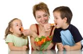 Woman feeding kids with fresh vegetables - the joy of eating healthy food poster