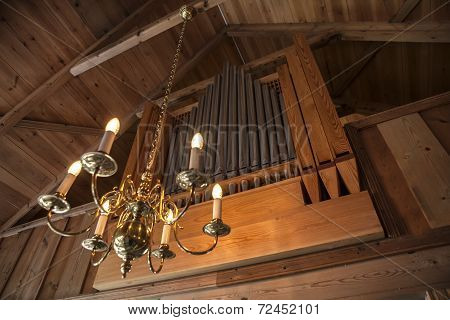 Pipe organ in an old wooden chapel with a pendant light poster