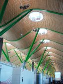 a large aiport ceiling with a wavy pattern well illuminated and modernly shaped green columns. poster