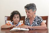 Grandmother teaching the Holy Bible to her grandson. Hispanic family studying the word of God in their daily Christian devotional. Reverence to God learning from His word. poster