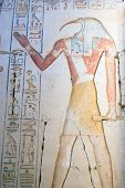 Large painted carving of the ancient egyptian god Thoth.  Depicted with the head of an ibis bird, Thoth is the god of wisdom and writing.  Wall at the ruined Temple of Ramses II at Abydos, Egypt. poster