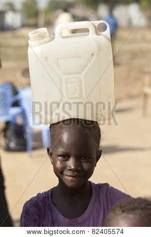 BOR, SOUTH SUDAN-DECEMBER 3, 2010: Unidentified child carries a large water container on her head.