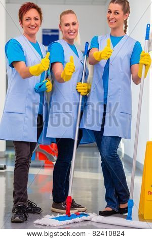 Cleaning ladies working in team showing the thumbs up sign