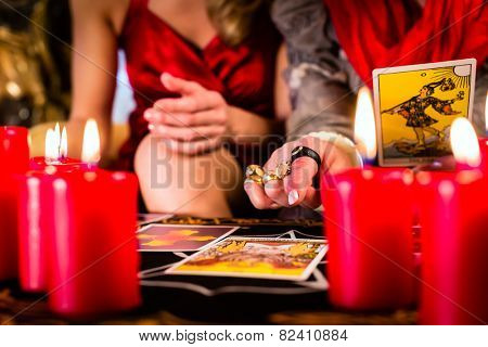 Fortuneteller laying Tarot cards with client on pentagram, candles are burning