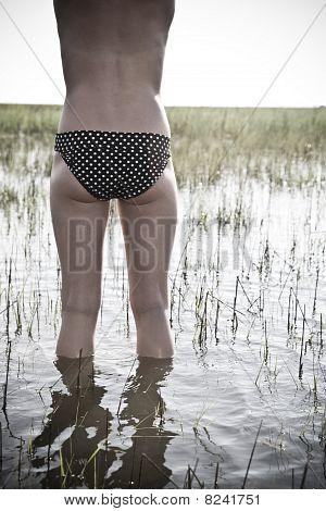 Young Woman in Bikini Bottoms Standing in the Marsh